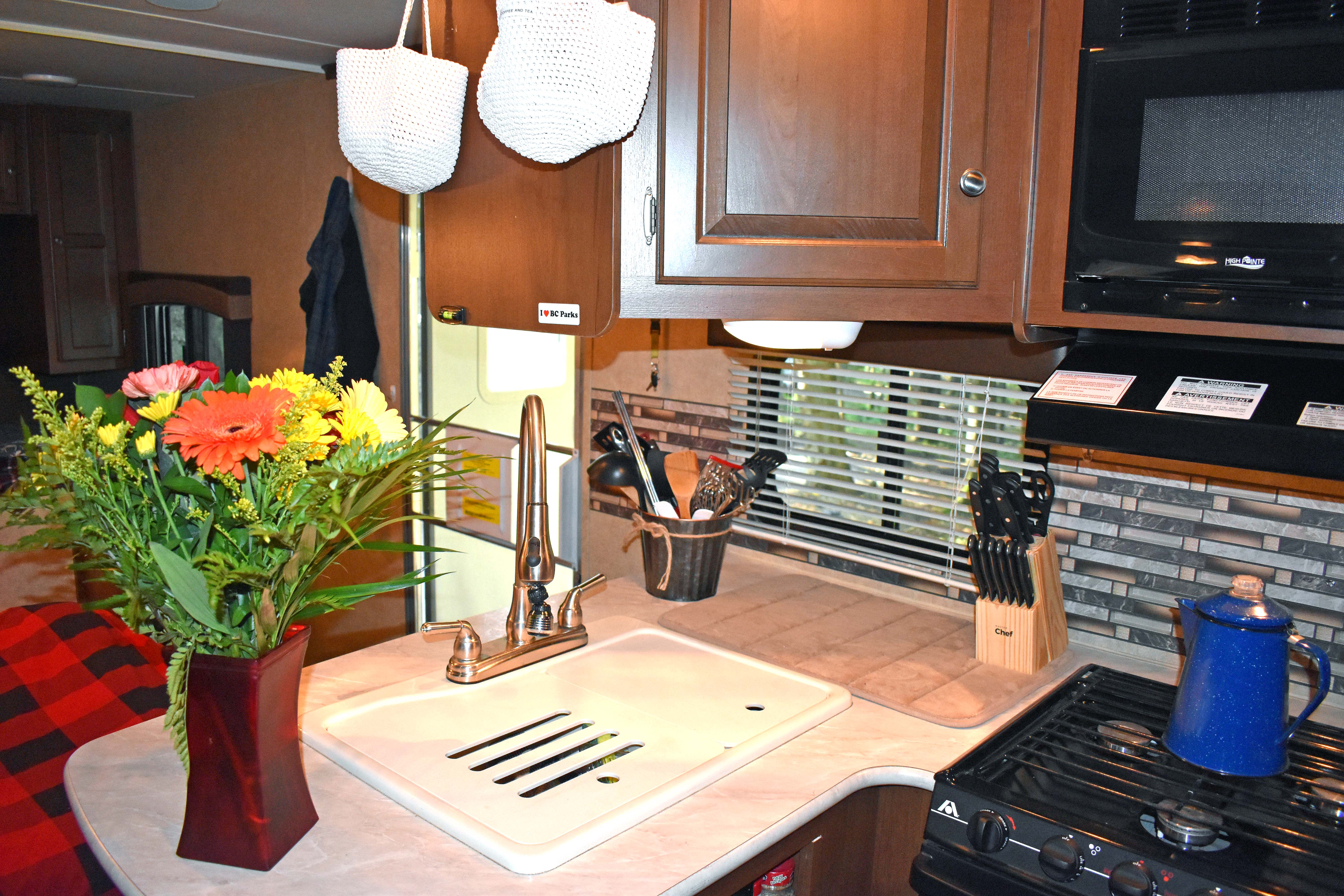 Full kitchen with large sink, 3 burner stove, microwave, small oven, mid-size fridge an freezer. Jayco Jay Flight 2014