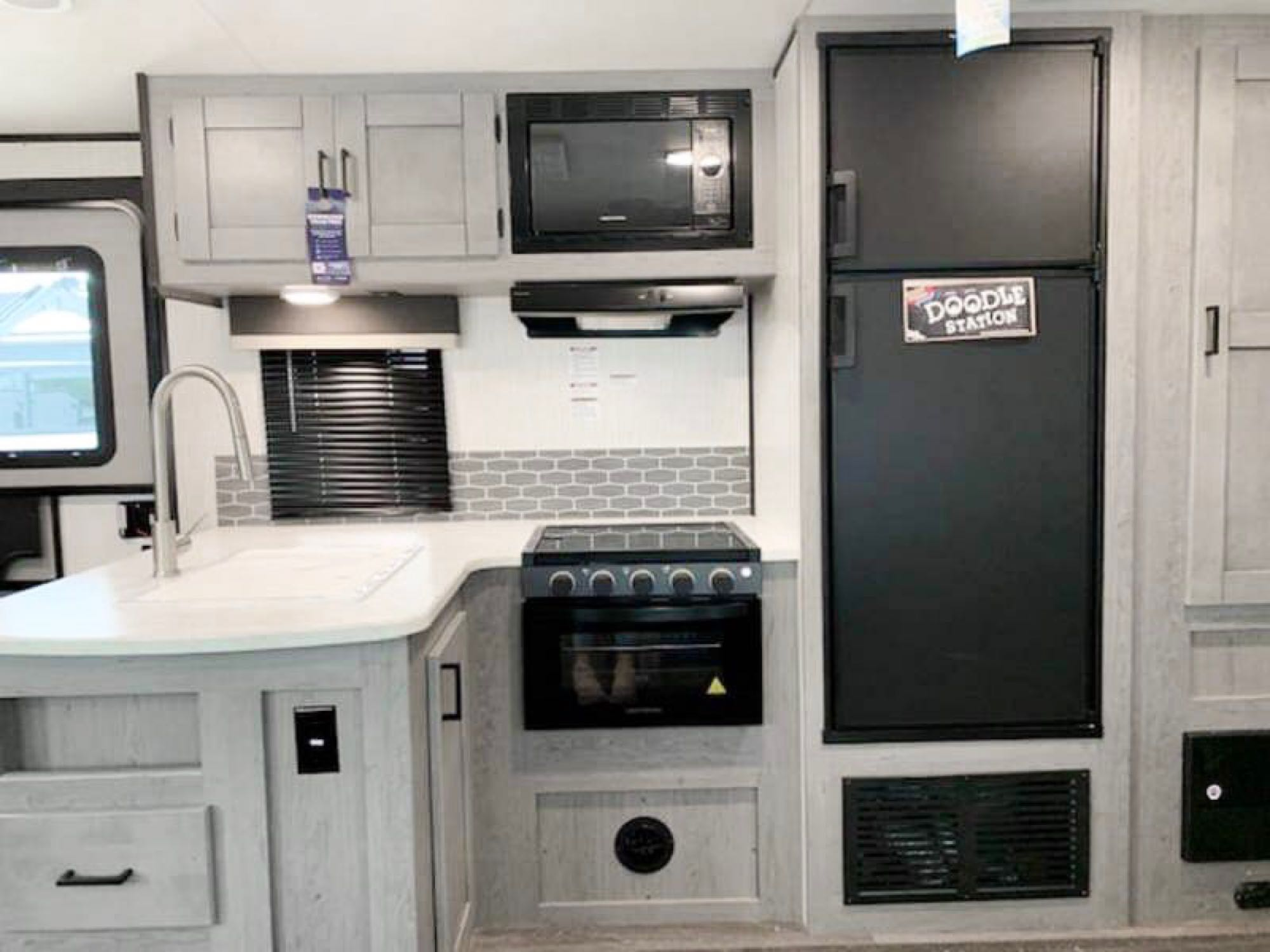 Feel right at home with a refrigerator/freezer, microwave and stove/oven! Sink has a pullout faucet. Heartland Mallard 2021