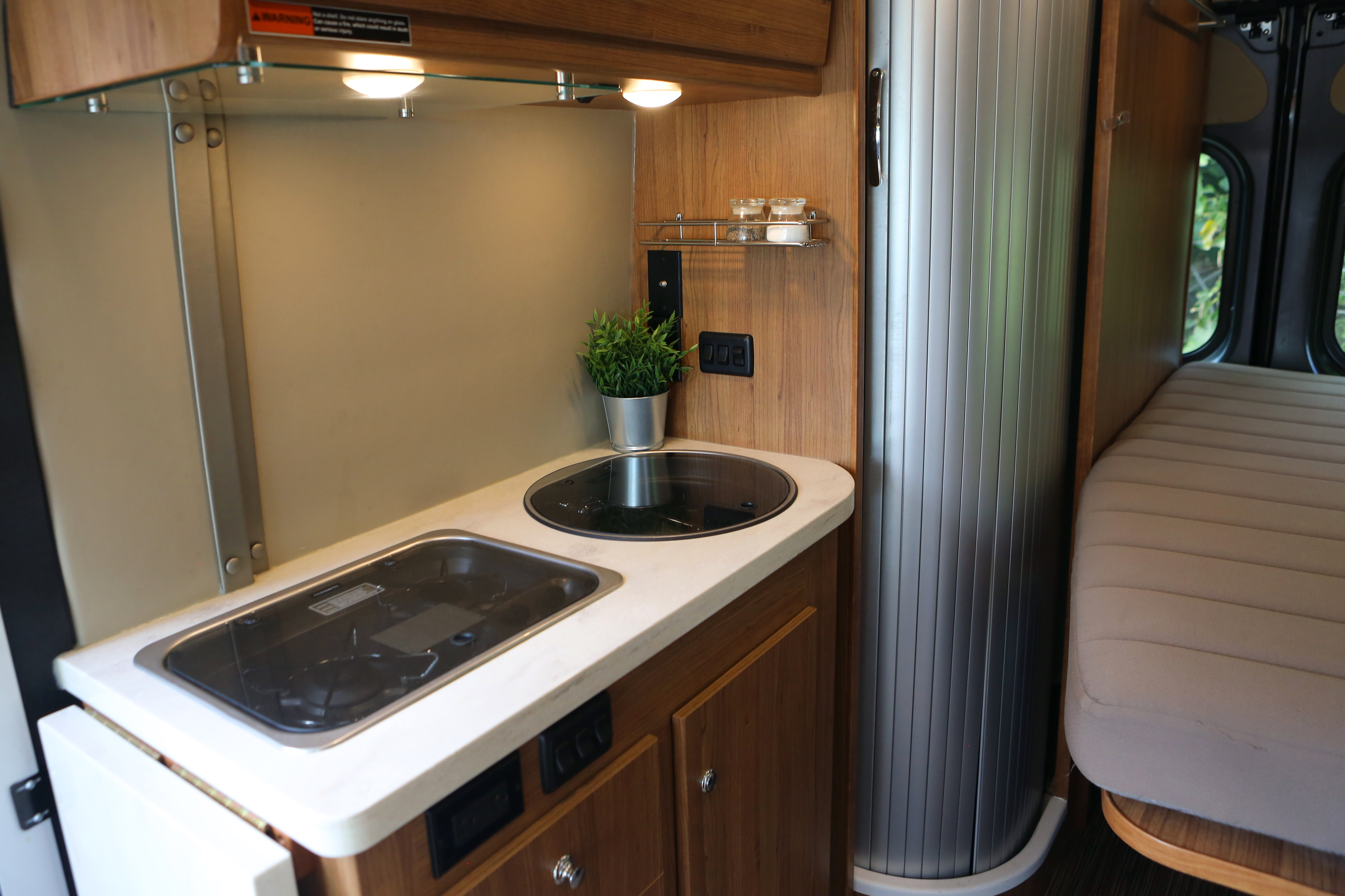 The full galley includes a two-burner range with a glass cover, a microwave oven to handle cooking duties, with stainless steel sink.. Winnebago Travato 2018