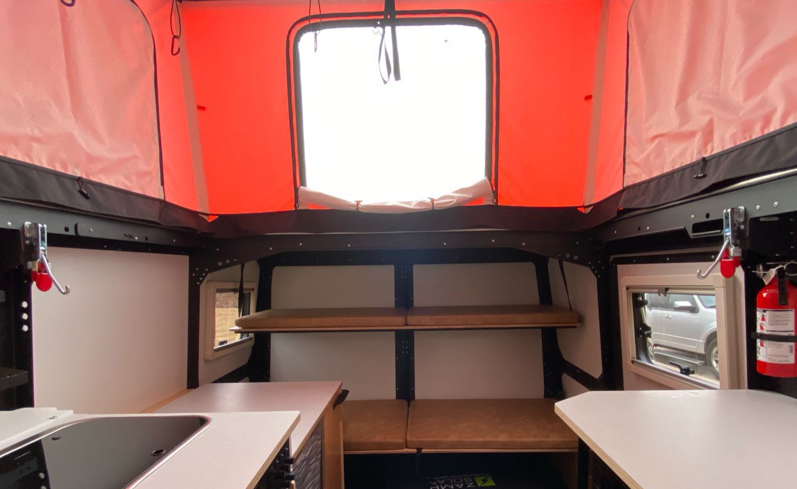 The bunk beds can be lifted secure against the wall for extra space or storage. The top bunk also has a safety net.. TAXA Outdoors Mantis Camper 2021