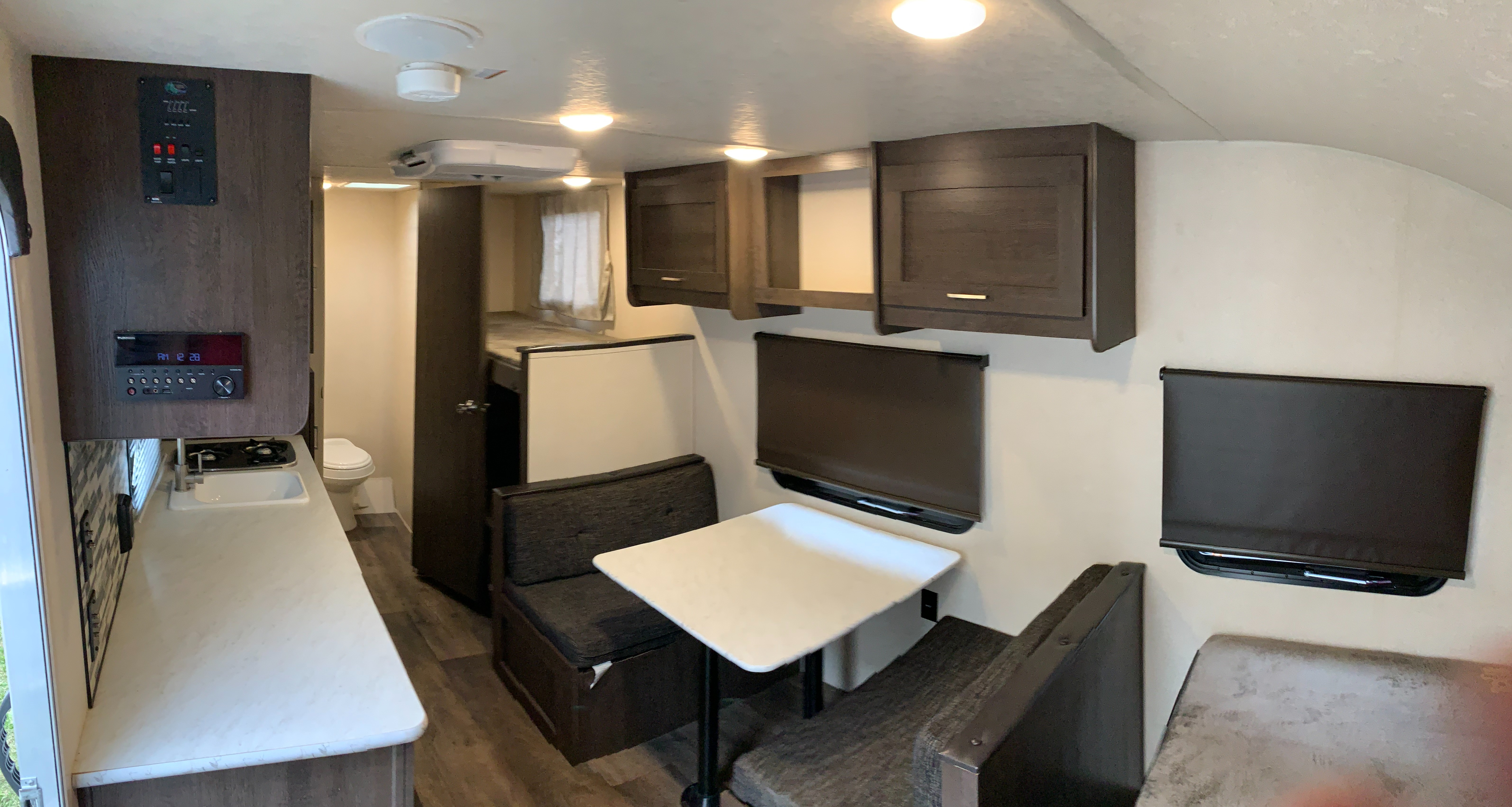 Four person dinette with window and overhead cabinets. Forest River Wildwood X-Lite 2018