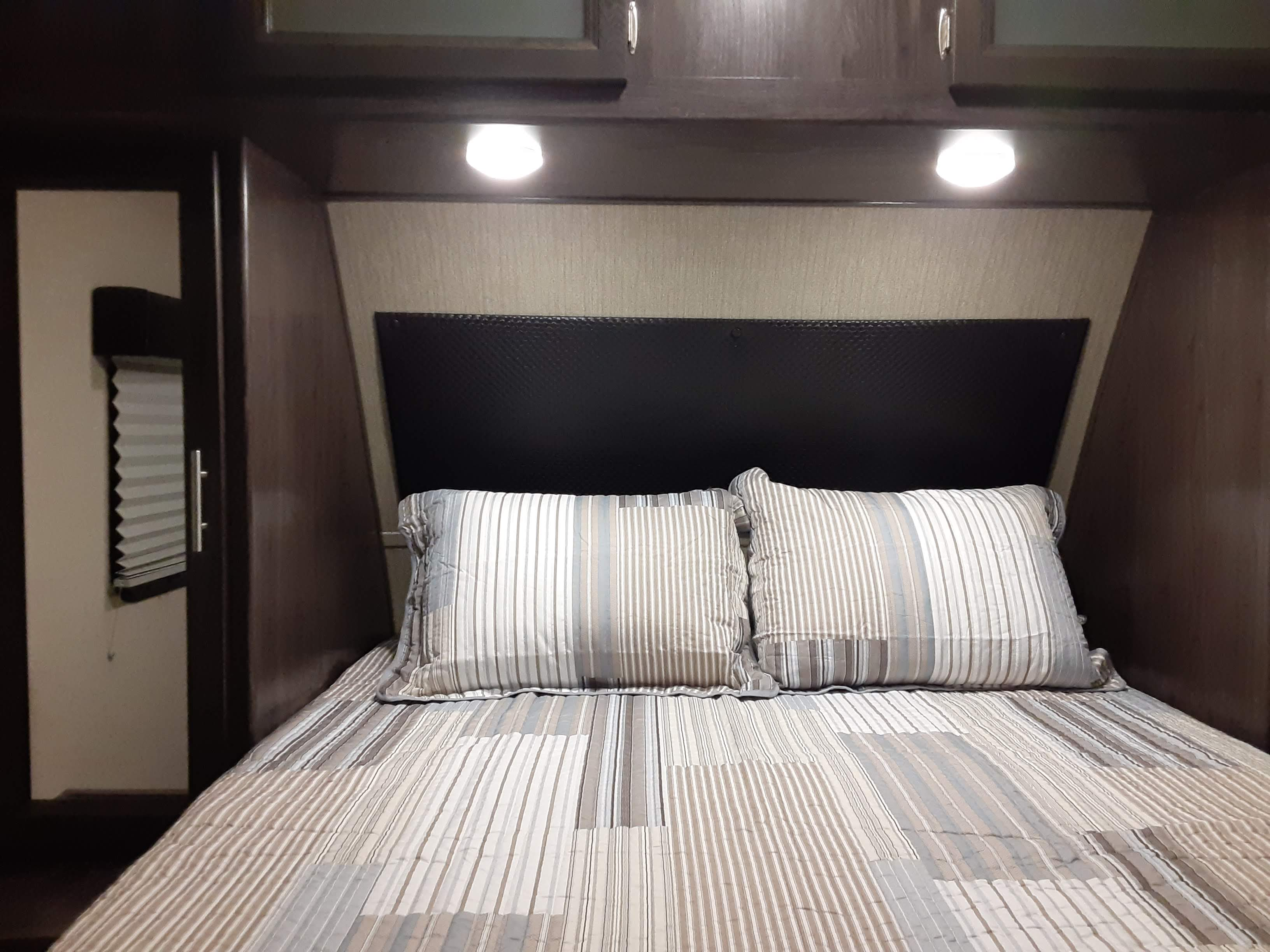 Queen bed, with wardrobe closet on each side as well as overhead cabinets & pocket door for privacy. Separate outdoor entrance into bedroom.. Dutchmen Kodiak 2018
