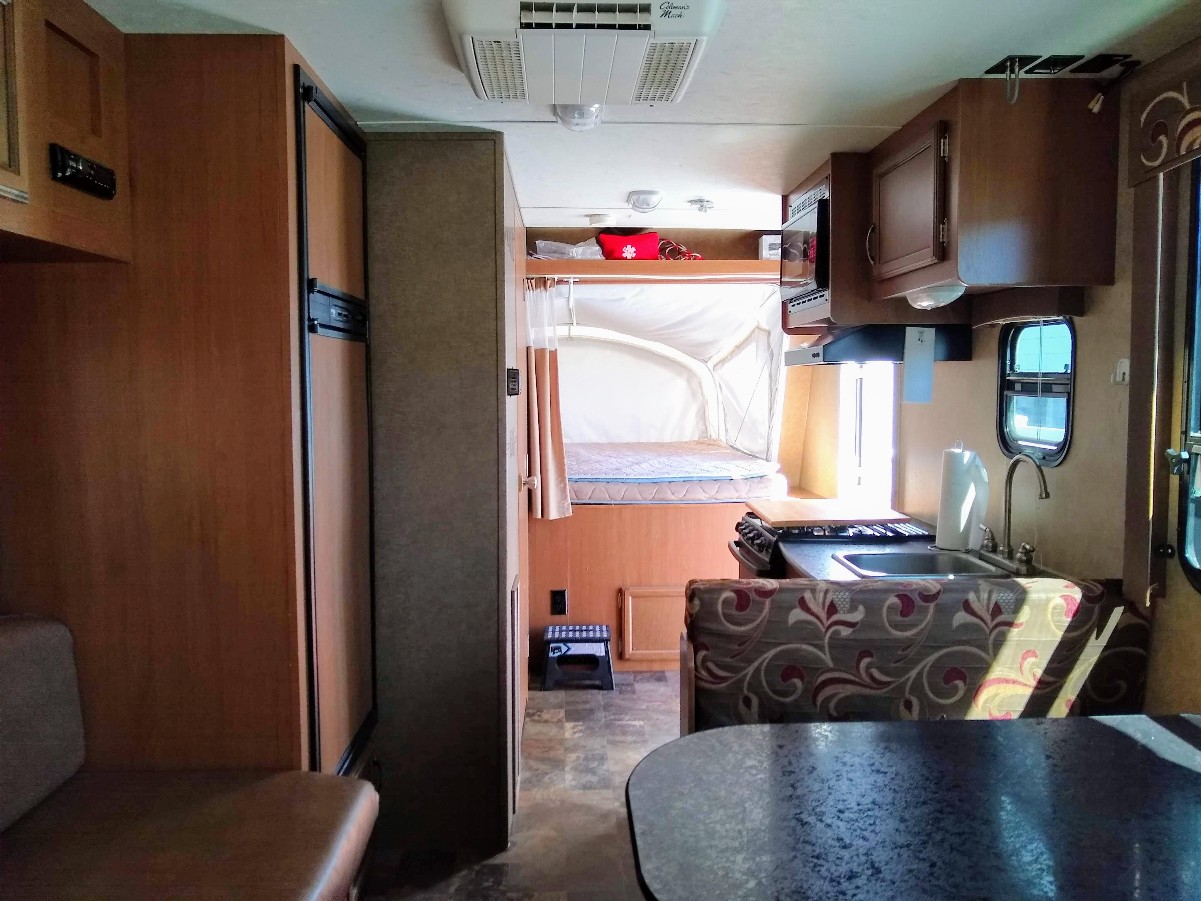 Standing in the back looking to front. The fridge and freezer on the right, behind the bathroom. Notice step stool to help get up to the front bed.. Starcraft Travel Star 2014