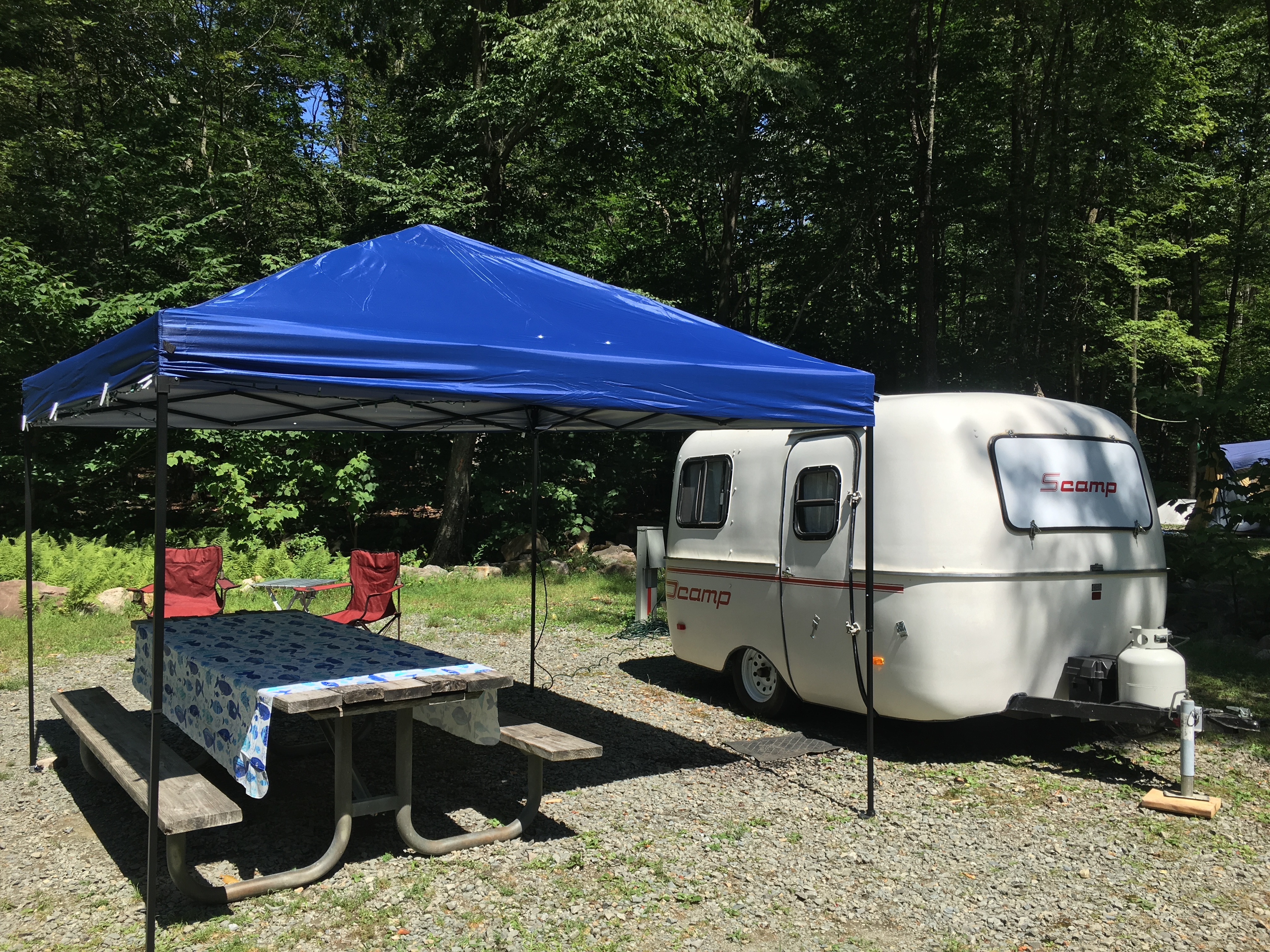 Scamp All American trailer with pop up awning, camp chairs and table cloth - all included in rental (picnic table not included). Scamp 13' 1985