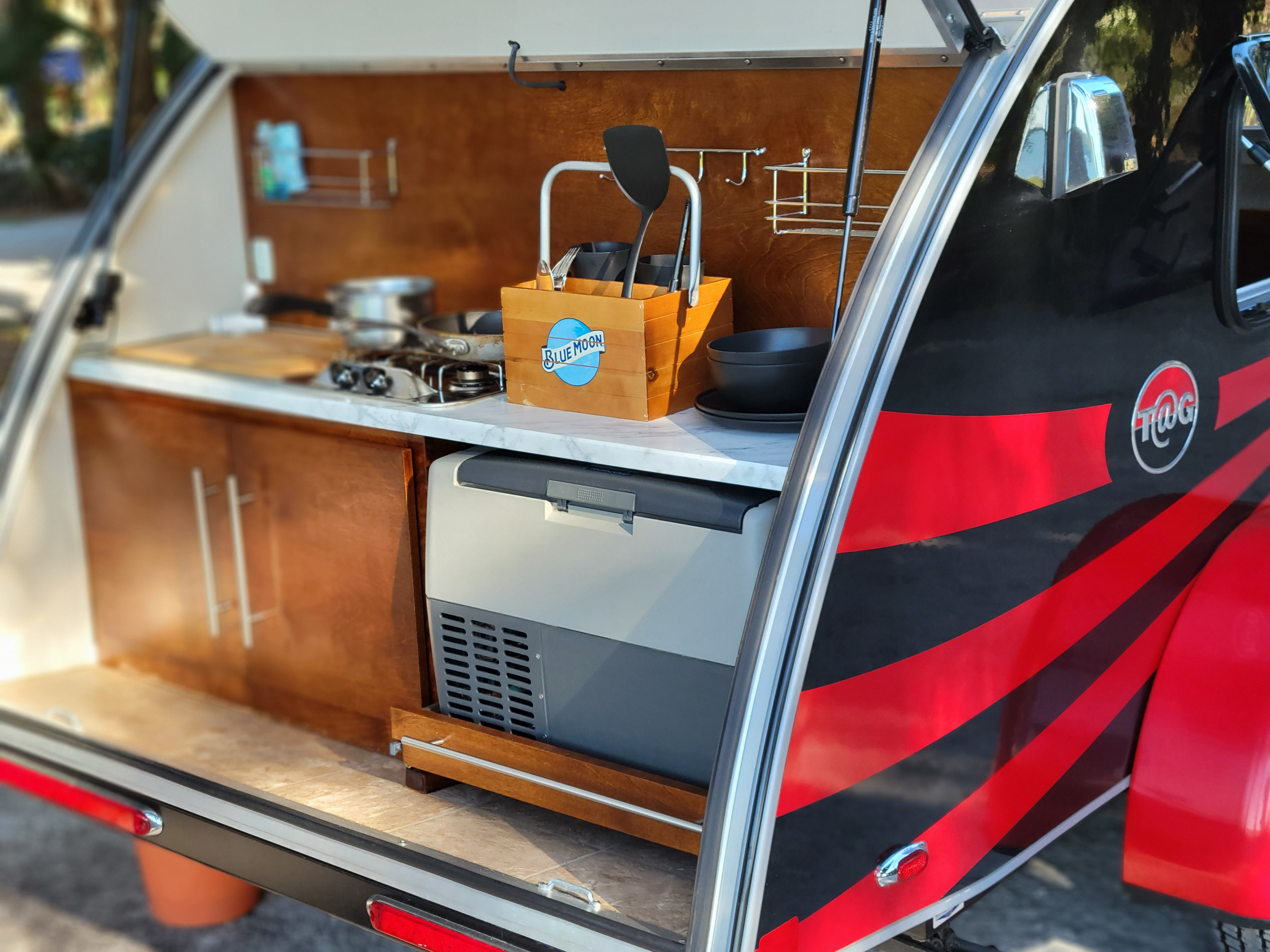 Cook your meals from the back galley of Tails. Kitchen includes 2 stove top burners, a refrigerator, and sink, and basic cooking utensils for two. . NUCAMP T@G 2018