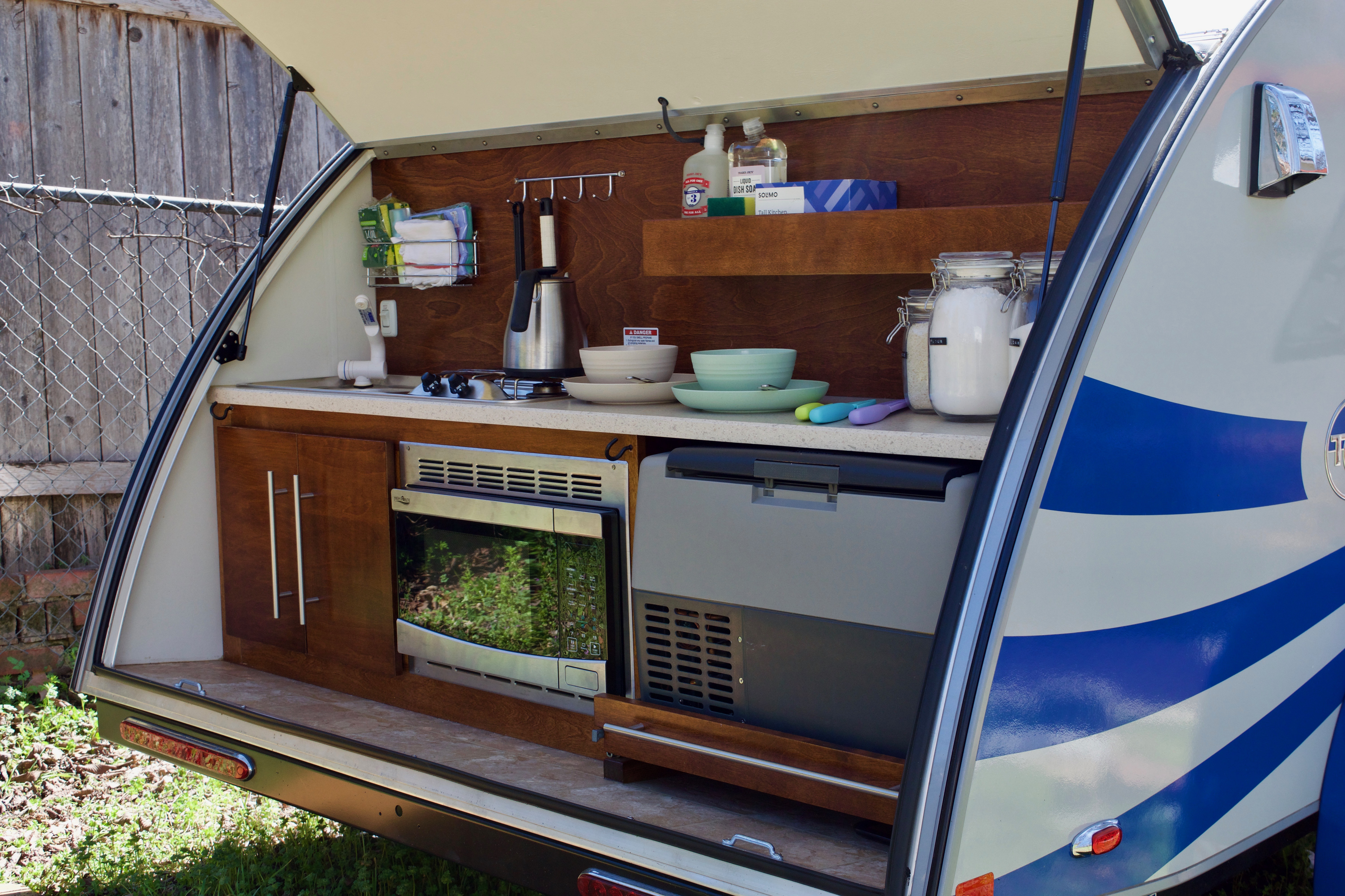 Spacious outdoor kitchen with microwave, fridge, two burner stove, and sink. T@G XL 2018