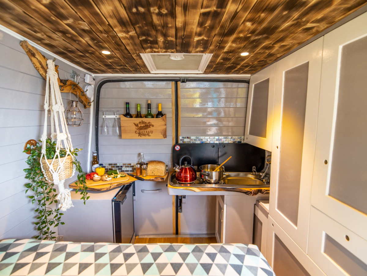 Photo taken from front of van, looking back towards the closed rear doors. When the rear doors are closed, you can cook whilst sat on the rear bench of the sofa bed (just visible in the foreground,) with your knees tucked under the worktop which has hobs mounted in it.