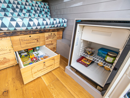 A peak inside the new Dometic fridge/freezer, and showing some of the reclaimed wine box under-bed storage and newly upholstered sofa-bed cushions.