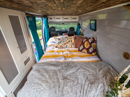 This shows the double sofa-bed in bed mode. Also shows the copper curtain rails and the storage cupboards on the left, as well as more storage above the cab.