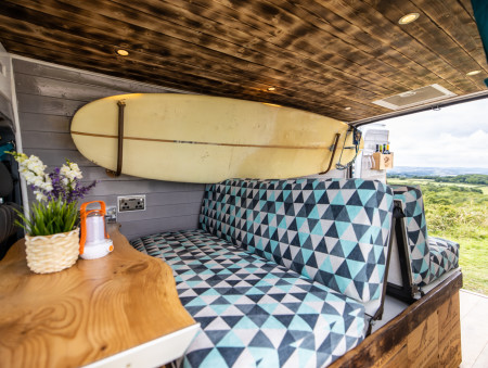 Taken from outside of the side door, this shows the sofa bed, fixed wooden table and the surfboard rack in action. Also the Shou Sugi Ban (burnt wood) ceiling.