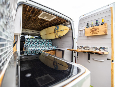 A view from behind the van. The two tinted glass worktops in the foreground lift up independently of one another to reveal 2 hobs and a sink. These are mounted into a live edge redwood worktop. A further wooden worktop and wine rack are mounted on the inside of the other rear door. Iridescent mosaic tiled backsplashes also in the foreground. sofa-bed, surfboard (on its rack) and cupboards above the cab in the background.