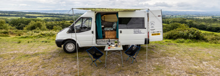 Side view of the van, along with awning and camping furniture.