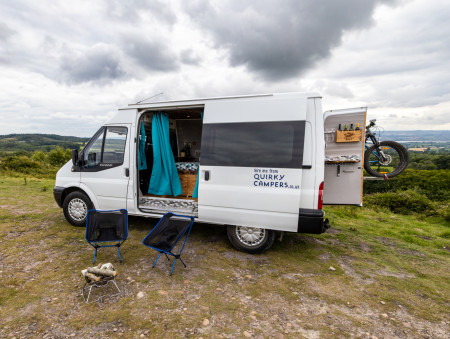 Side view of van, with one rear door open. BBQ/fire pit and camp chairs in the foreground.