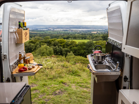 The view, looking out of the open rear doors. This shows the tinted glass covers tilted up, enabling the 2 hobs and sink to be used. Also shows the work space on the other worktop. You can cook whilst stood up, outside of the rear of the van.
