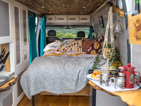 Looking into the van from the open rear doors, at the sofa-bed in bed mode. (Breakfast on the rear right worktop!)