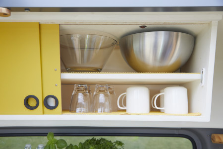 Kitchen cupboard with serving bowls, tumblers and mugs.