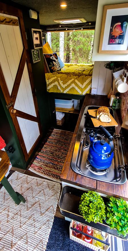 Interior floorplan view of kitchen, bed, storage and toilet door