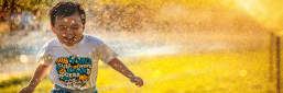 A kid playing in the sun with water