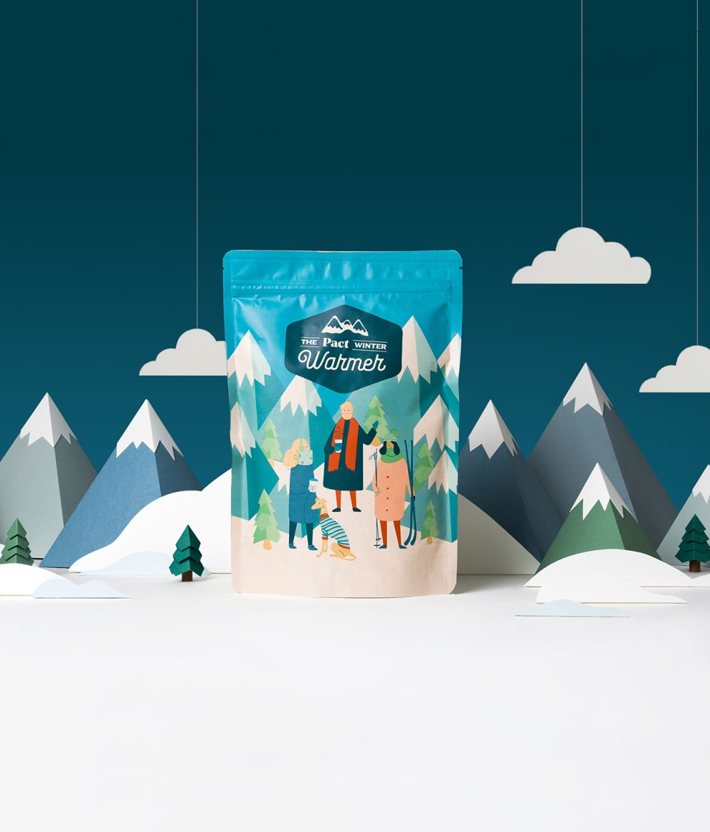 Pact Coffee's Christmas Blend on a snowy background with clouds and mountains