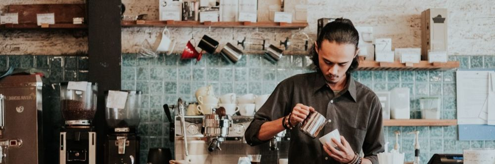 A barista in a cafe about to pour coffee