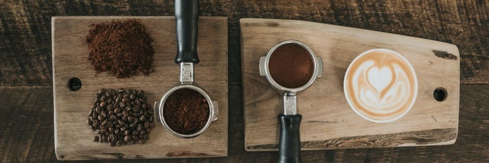 Four different coffee grinds and a cup of coffee on a bread board