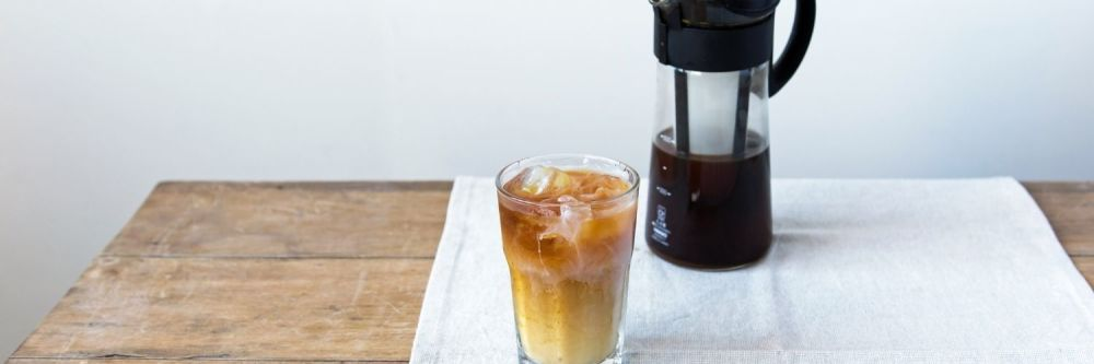 An iced coffee and half full coffee pot on a table