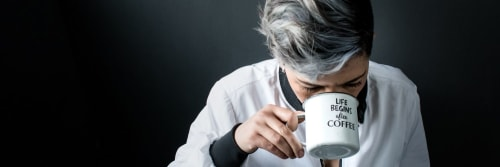 Woman drinking from a mug reading 'Life Begins after Coffee'