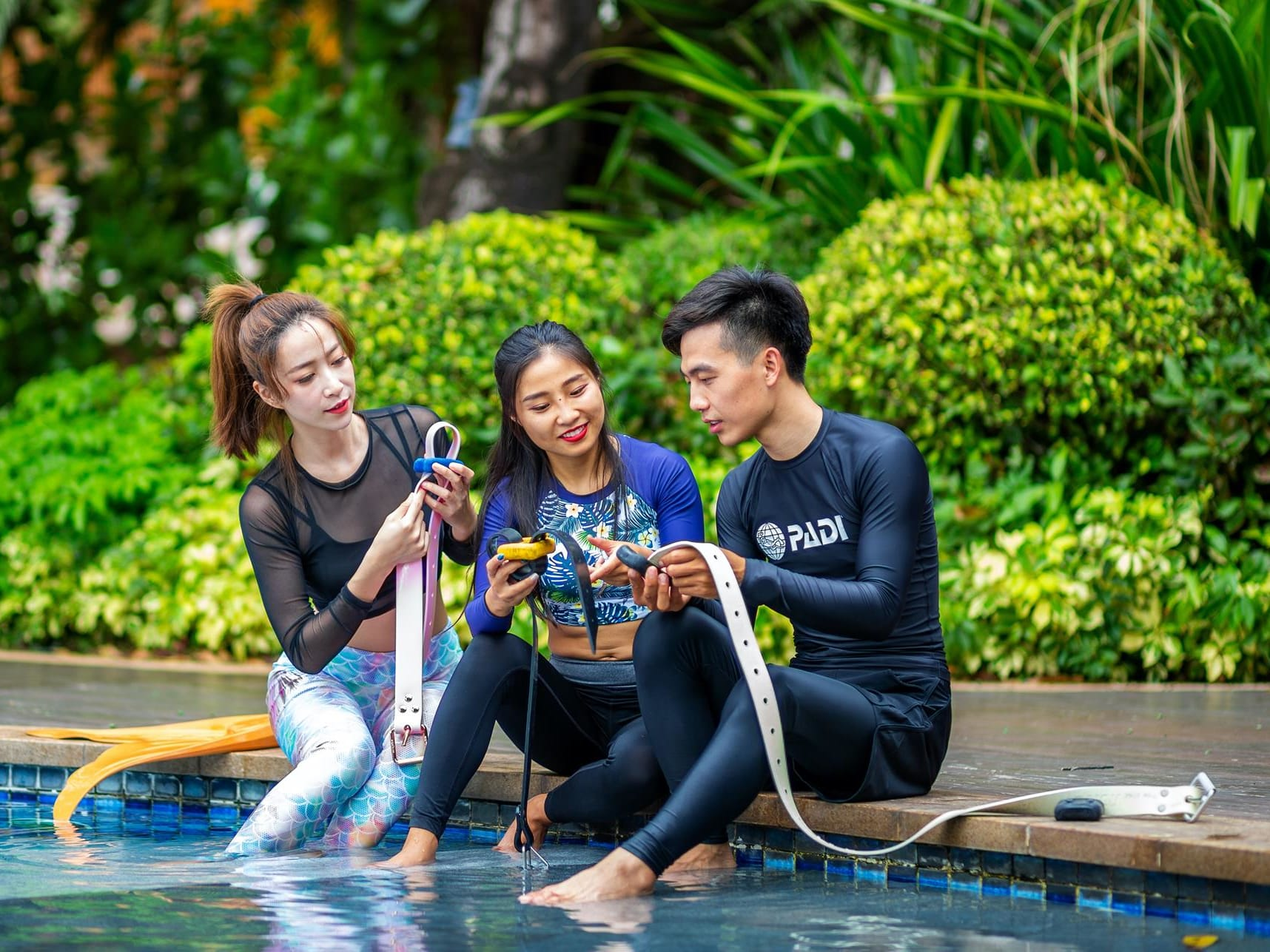 Divers by pool with mermaid diver