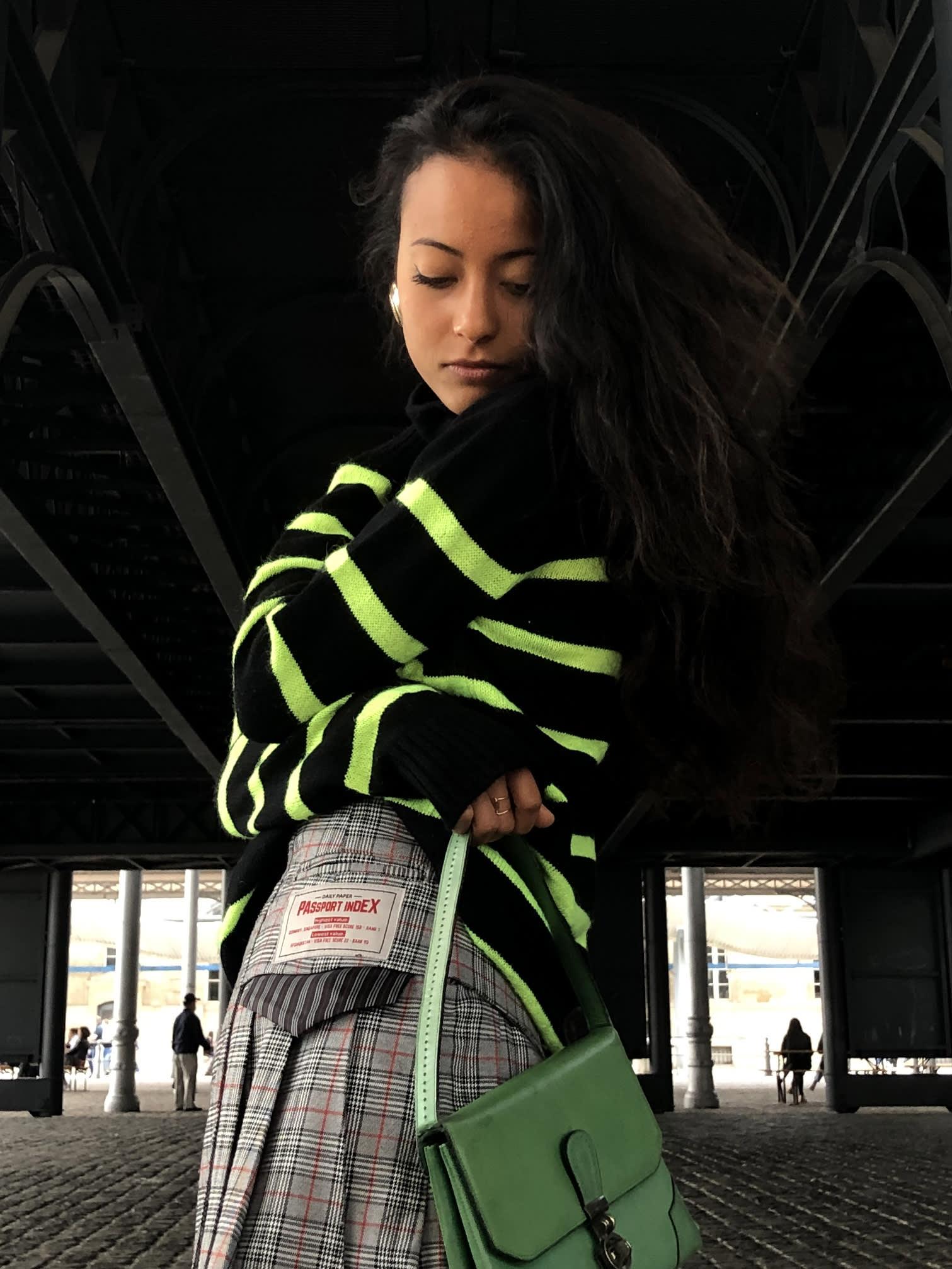 Modèle qui porte le produit Jupe Plissée Asymétrique à Carreaux de la marque Daily Paper
