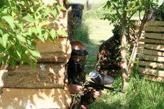 Dwóch graczy w paintball ukrytych za drewnianymi domkami w cieniu