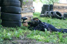 Gracz w paintball leżący na trawie i celujący zza opon