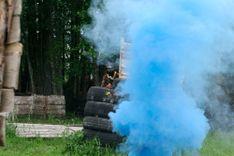 Niebieski dym świecy dymnej zasłania gracza paintballowego
