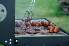 Kiełbaski i karkówka smażące się na grillu