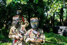 trójka chłopców w maskach paintballowych wychodzących z cienia drzew