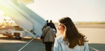 Woman boarding flight from apron