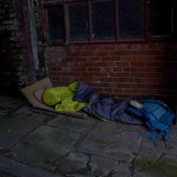 A blue sleeping back and rucksack are on the floor underneath a window