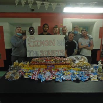 A group of people holding a Simon on the Streets sign in front of a table of food