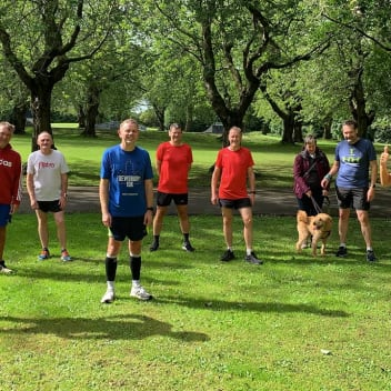 Nine people and a dog standing in Armley Park fundraising money for Simon on the Streets.