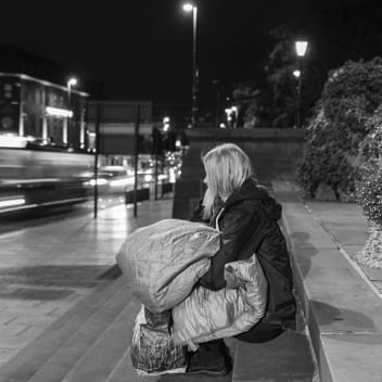 A woman sits on a set of steps. She is holding a sleeping bag and looking at the traffic passing by.