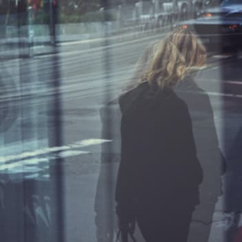 woman walking across a street. The image is blurred and the woman is looking away.