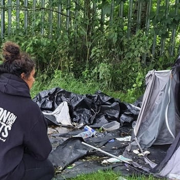 A woman is crouched next to the entrance of a tent. Her back is turned and she is wearing a Simon on the Streets hoodie.