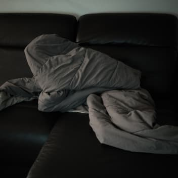 A black and white photo of a duvet on a sofa