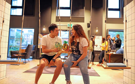 Two students share a drink in a social space at their student accommodation