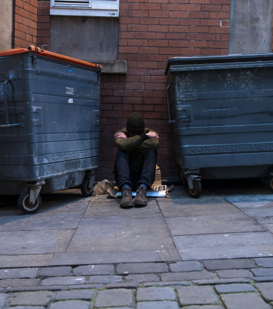 A person is sat on the floor between two bins.