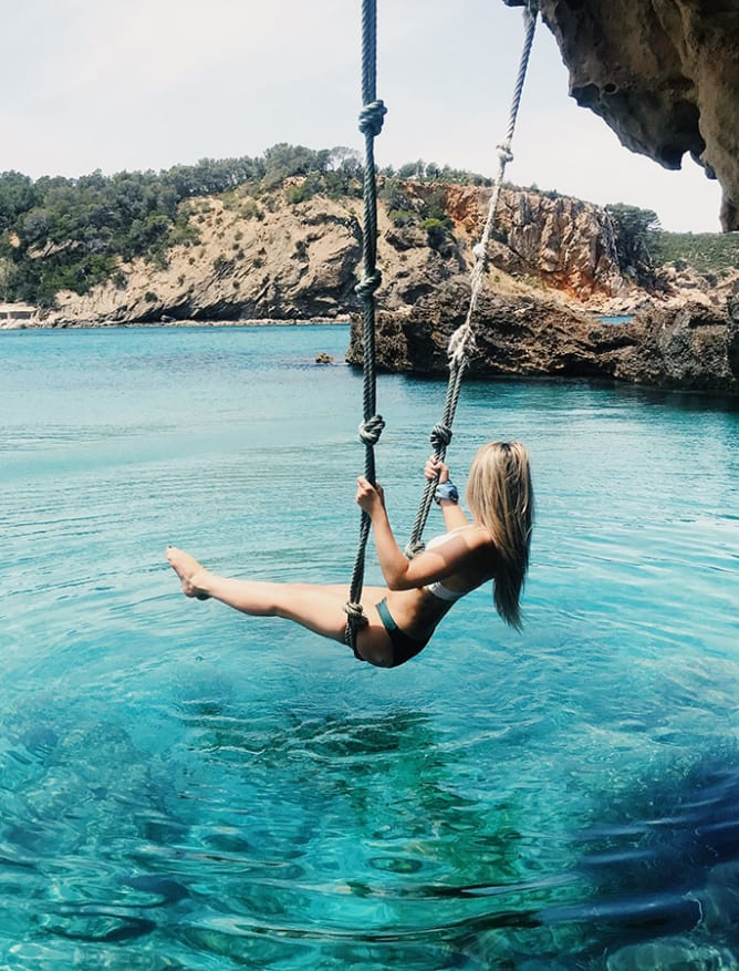 Rope swinging over clear waters in Ibiza