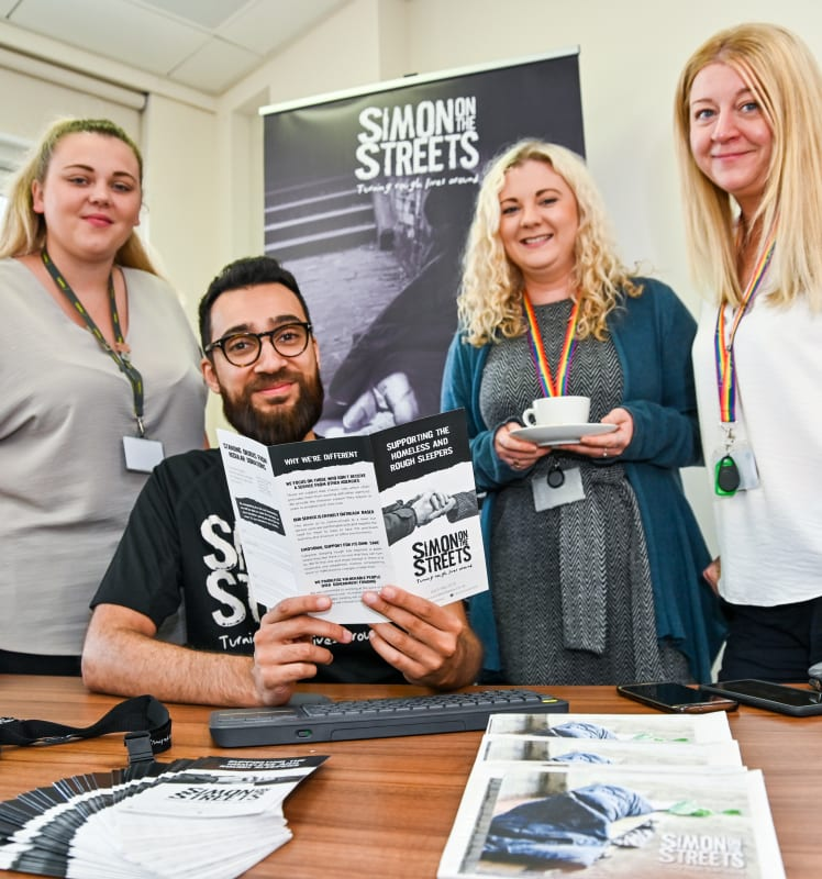 4 people at a table, looking at Simon on the Streets leaflet
