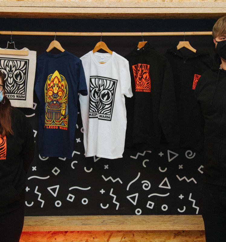 Two people stand either side of Keep Leeds Warm Merch