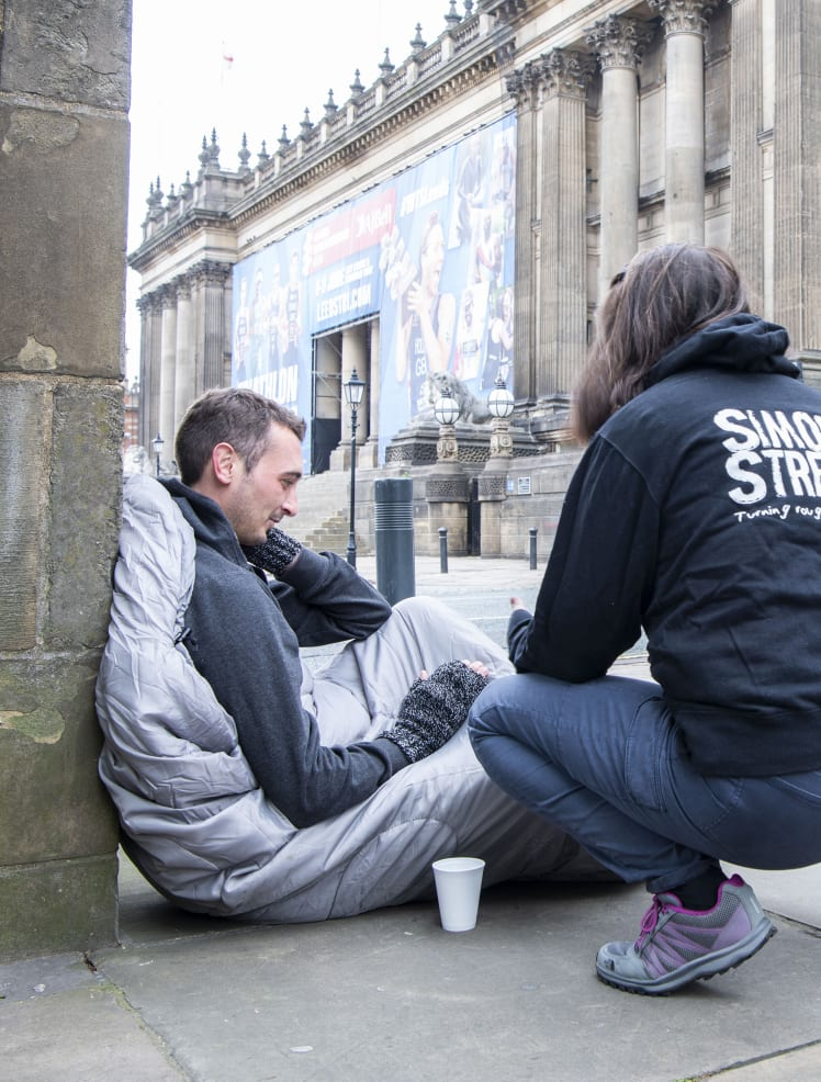 An outreach worker is bent down talking to a man in a sleeping bag