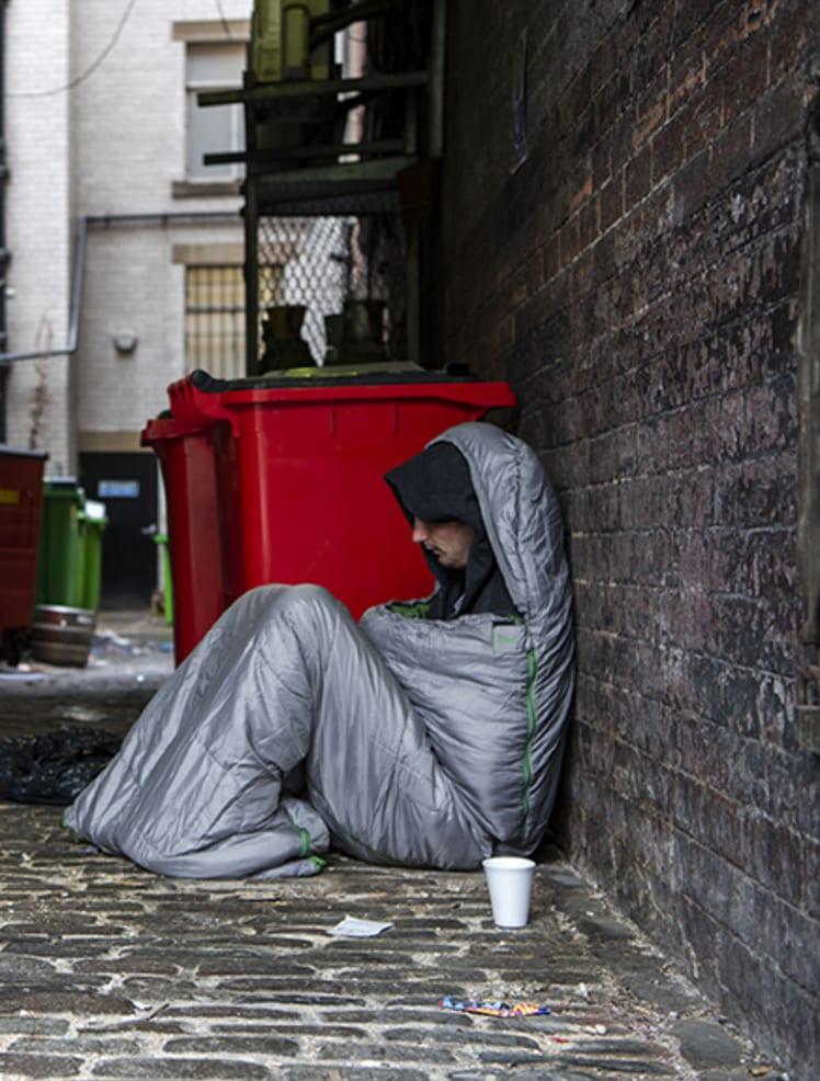 Man in sleeping bag in alley way