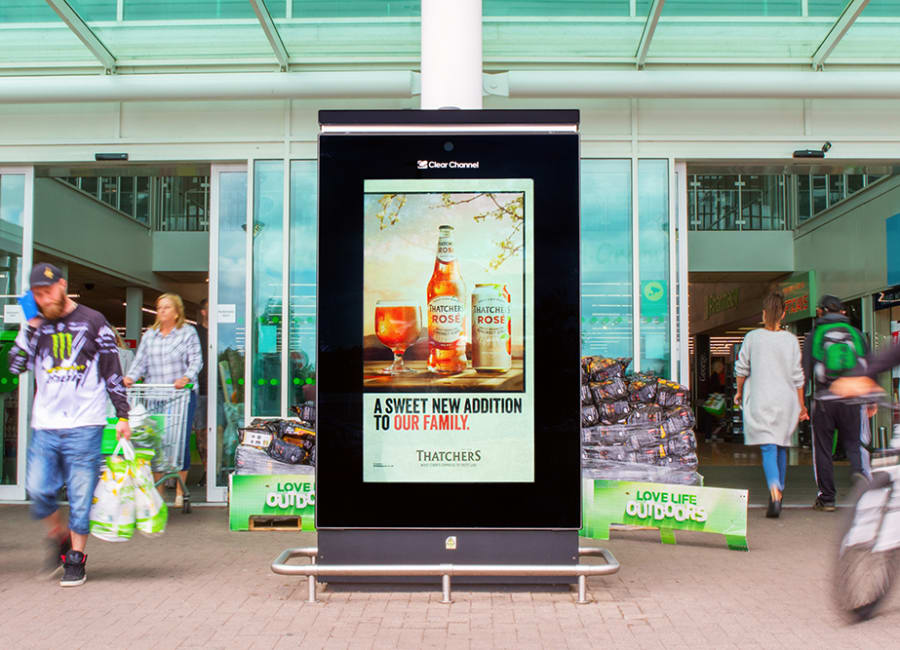 Shoppers outside Asda with digital screen
